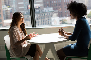 Two women talking in a business meeting.