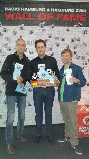 Zu Besuch bei Radio Hamburg: Claus Knupper überreicht John Ment und Fabian Kühne seinen Snackholder