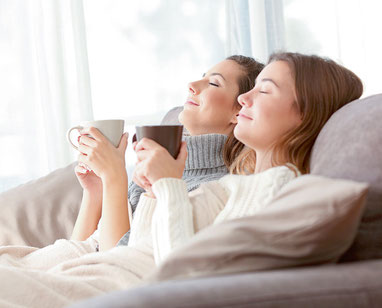 Zwei Frauen sitzen entspannt und zurückgelehnt mit einer Tasse Tee auf der Couch