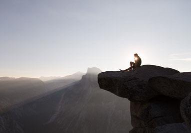 Mann sitzt auf Felsvorsprung