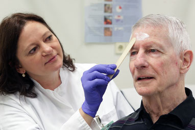 Prof. Dr. med. Sigrid Karrer trägt bei einem Patienten die MAL-Creme auf.  (Fotos: UKR)