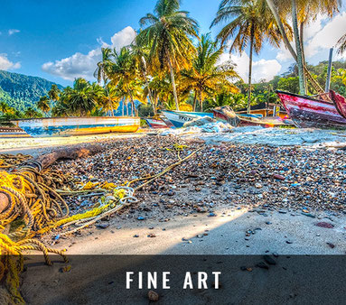 Several small fishing vessels called pirogues are lying on a stony section of the beach with old yellow rope and logs forming a kind of Caribbean Fine Art.