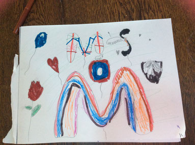 photo of a drawing done by a child. There is a rose, a heart balloon, a balloon, and the letters MOMS