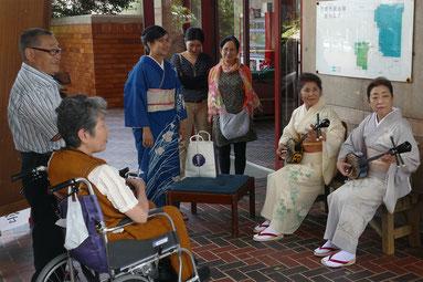 審査を前に会場周辺で三線を演奏する人たち=1日午後、市民会館