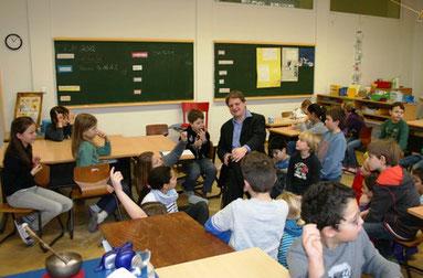 Witzel erörtert mit Grundschulkindern die Funktionen des Geld und Risiken der Verschuldung.