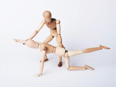 Zwei Holzpuppen stellen dar, wie ein Patient in der Yoga-Therapie vom Yoga-Therapeuten unterstützt wird. Bild Clemens Schüßler/Fotolia