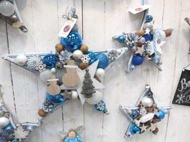 Blau-weiß Sterne als Weihnachts Dekoration an weißer Holzwand.
