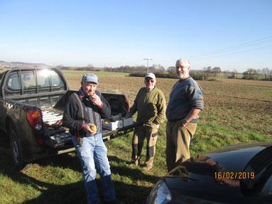 Gruppenbild am Pickup-Truck, ein Acker im Hintergrund