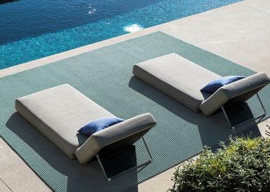 Blick auf zwei Liegen am Pool auf einem Outdoorteppich von JAB Anstoetz