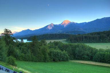 Dieses Bild wurde mit Standpunkt Gästehaus Gabriele aufgenommen und zeigt den Mittagskogel und den Türkenkopf und am Himmel sieht man schon fast den Vollmond
