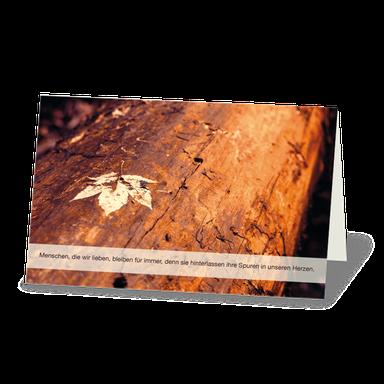 Trauerkarte  Holzstamm mit verwelktem Ahornblatt. Herbstfarben, orange und rötlich.