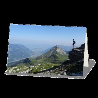 Trauerdanksagung mit Bergpanorama. Blick über ein Bergtal mit Bergen am Horizont. Ein Bergsteiger oder Bergwanderer betrachtet die Landschaft.