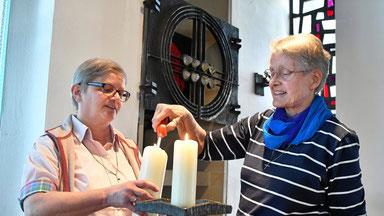 Schwester Martina Paul (links) und Schwester Stephani Orlowski zünden eine Kerze in der Kapelle an. An den Feiertagen verfolgen sie die Fernsehgottesdienste oder verteilen Ostergrüße in einer Tüte. (WAZ-Foto: Joachim Kleine-Bühning / FUNKE Foto Serivces)