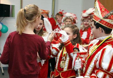 Prinzessin Merit I (Merit Römer) überreicht ihrer Nachfolgerin Prinzessin Xenia I (Xenia Zimmermann) die Insignien der Macht, Diadem und Blumenstrauß. Prinz Benedikt II (re.) trägt bereits die Narrenkappe auf dem Kopf und hält das Zepter fest in Händen.