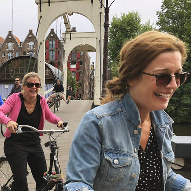 Ladies smiling as they cycle over an Amsterdam bridge on a bike tour