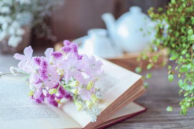 白磁のティーセット。ページが開かれた本のうえに無造作に置かれた紫の花。