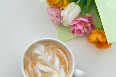 デスクに積まれた書籍のうえに無造作に置かれたピンクのチューリップ。