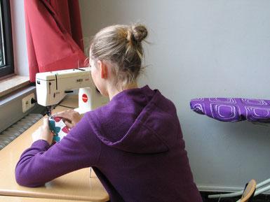 Schülerin der Nähwerkstatt beim Nähen einer Tasche