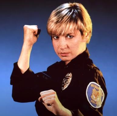 Cynthia Rothrock in Polizeiuniform vor blauem Hintergrund.