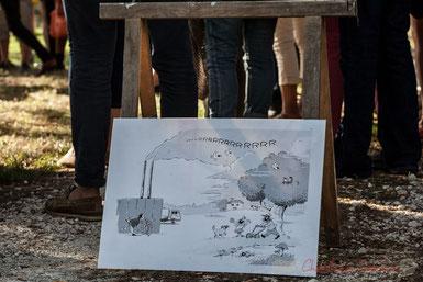 Dessin humoristique. Une personne hume une fleur au pieds d'une usine, tandis que les fumées vont vers la campagne ou le riverain comme ses animaux de ferme portent un masque à gaz.