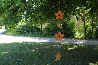 Girlande aus orange Holzblüten an einen Baum gehängt.