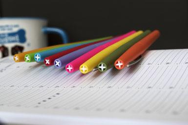 Verschiedenfarbige Stifte auf einem Kalender: Ein gut organisierter Korrekturumlauf minimiert die Fehler in Printprodukten.