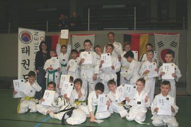 Zufriedene Gesichter in der Kindergruppe sowie Prüferin Carmen Spiekermann (links) und Trainer Jörg Krieter (mitte)