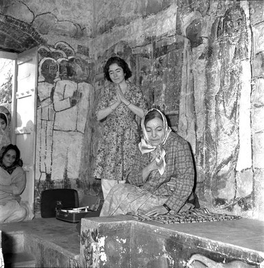 "Mehera with Mani Irani ( standing ) and Roda Mistry viewing Meher Baba in the crypt on January 31st 1969. On the floor, the record player is playing ""Begin the Beguine"" by Hutch Hutchinson, this was played 7 times as per Baba's instructions."