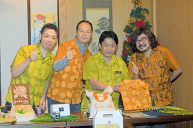 石垣市特産の開襟シャツを身に着け、商品を前に、FB登録を祝う樋渡武雄市市長(右から3人目)ら=ゆんたく屋、大川