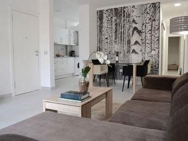 Wohn- und Esszimmer mit einer gemütlichen dunklen Couch