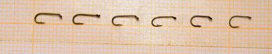 Alcuni esempi di amo #22, fotografati su carta millimetrata per meglio comprendere le dimensioni. Da sinistra: Tmc 100, Tmc 101, Daiichi 1100, Mustad Signature R30, Partridge L3A, Varivas 2300. Notate le dimensioni maggiorate dell'occhiello del Daiichi