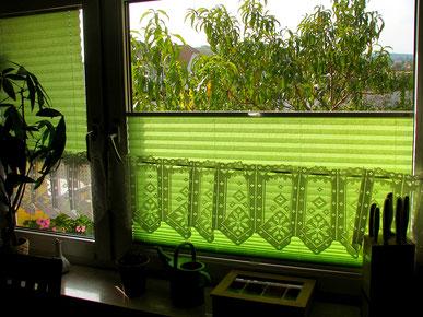 Lindgrüne Plissees in der Küche schützen an heißen Tagen vor zu intensiver Sonneneinstrahlung.