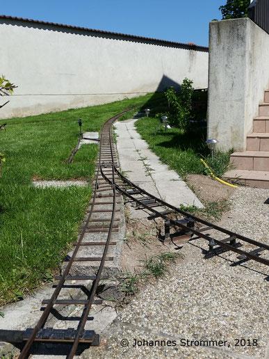 Abbildung 8: Rückfallweiche meiner Gartenbahn 5 Zoll mit Radius 3.8 m; im Hintergrund die Steigung mit 12.5 %.