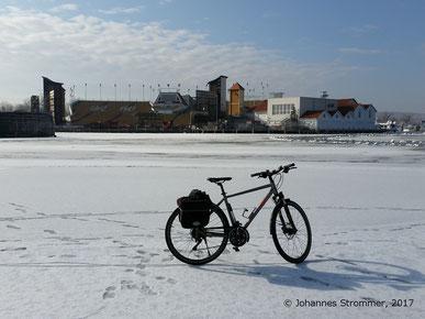 Fahrrad auf dem zugefrorenen Neusiedlersee vor Bühne der Seefestspiele Mörbisch.