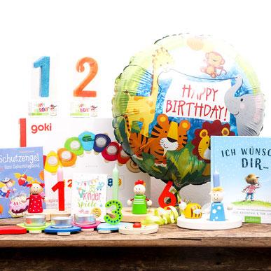 Geburtsags-Kerzen, -Bücher, -Ballons auf Tisch