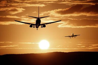 Flugzeuge bei Start und Landung im Sonnenuntergang