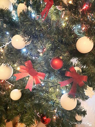 palline bianche, rosse fiocchi rossi su un albero di Natale verde