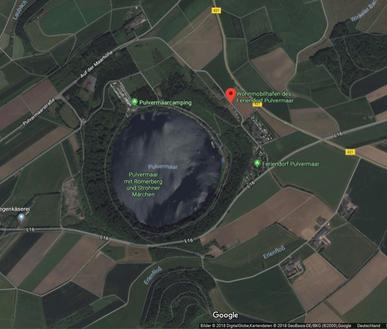 Die Luftaufnahme zeigt den nahezu kreisrunden Vulkansee