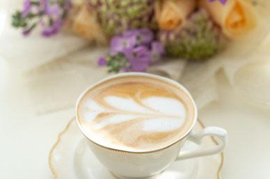 耐熱ガラスのティーポットとカップ&ソーサ。ガラスの花びんに活けられたマーガレットとチューリップ。ティータイムのひととき。