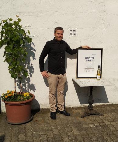 Weinküfermeister Philipp Wehweck nach Übergabe des Meisterbriefes 2019 mit seinem Meisterwein, welcher die Goldmedaille erhielt.