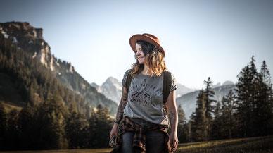 Junge Frau läuft über eine Wiese vor einer Bergkulisse im Hintergrund Wald und eine Bergkulisse festgehalten von der Familien Fotografin Monkeyjolie in Graubünden