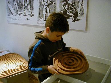 Ein Junge lässt die Murmel rollen in einem Holz-Labyrinth