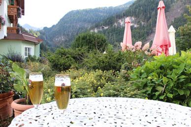 zwei Glas Bier auf Tisch vor Bergpanorama