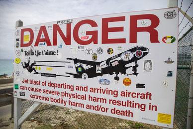 Il caratteristico cartello di avviso del Princess Juliana Airport e gli adesivi del PSC