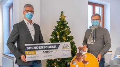 Alexander Bernhard, Geschäftsführer der SWAN GmbH (l.), übergibt die Spende seiner Beschäftigten an Thomas Kleist, Geschäftsführer von LICHTBLICKE e.V. (Bildrechte: SWAN GmbH)