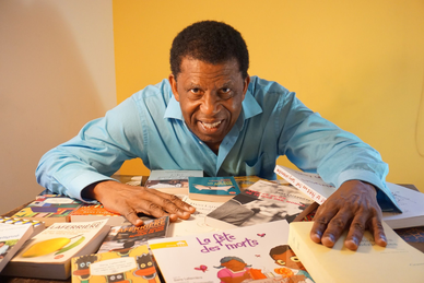 Das Bild zeigt den Autor Dany Laferrière hinter einem Tisch voller Bücher.