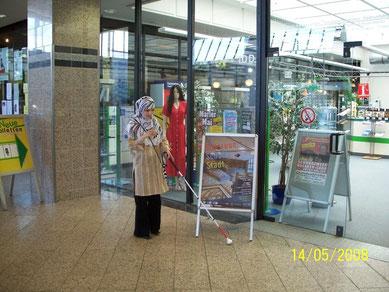 Junges Mädchen mit Langstock in einem Einkaufszentrum. Hier schützt der Langstock vor herumstehenden Werbeplakaten.