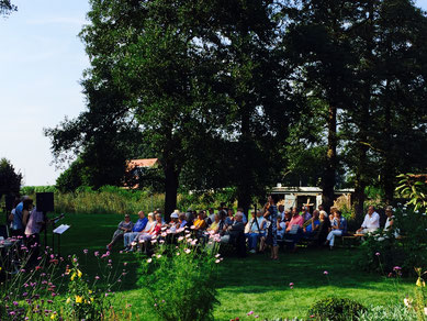 Auf einer grünen Wiese, von hohen Bäumen gesäumt, sitzen zahlreiche Zuschauer*innen und lauschen einem kleinen Konzert.