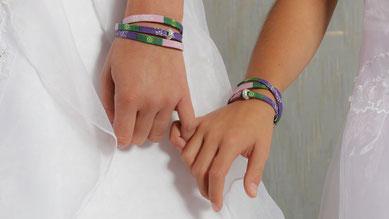 Mutter und Tochter reichen sich die Hände und tragen Stoffarmbänder um die Handgelenke