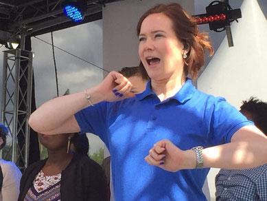Zu sehen ist eine Situation auf der Bühne. Ich dolmetsche einen Chor. Es ist sehr sonnig und ich trage ein blaues T-Shirt.
